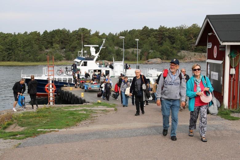 Matkalaiset Öröön kuljettanut vesibussi purkamassa lastiaan, vieressä on vierasvenesatama.