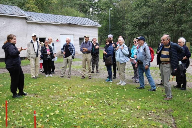 Opas kertoo Örön rakennuskannasta - taustalla saaren vesilaitos.