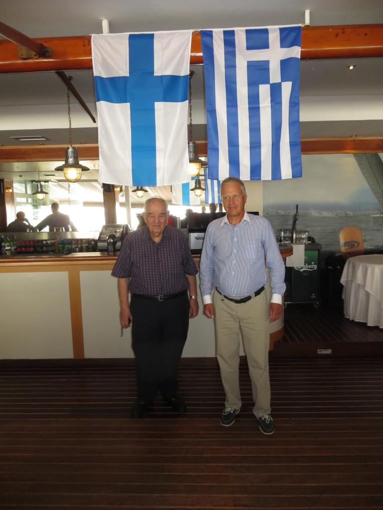 Kreikan Satamakapteenien klubin puheenjohtaja merikapteeni Marinos Tsamis Suomen lipun alla ja SJ-perinneyhdistyksen puheenjohtaja Juhani Toikka Kreikan lipun alla.