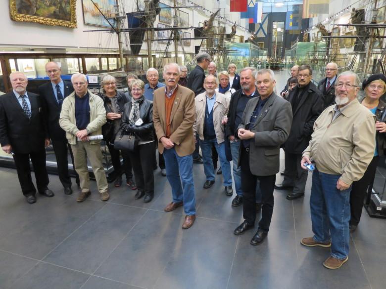 Matkailijat ryhmäkuvassa taustanaan Pietari Suuren salin pienoismallit, liput, taulut ja keulakuvat. Kuvassa vasemmalta ensimmäinen on museon opas ja kolmas paikallisopas ja tulkki.